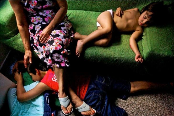 İtalya Sardunya'da bir anneanne torunları uyurken izliyor.