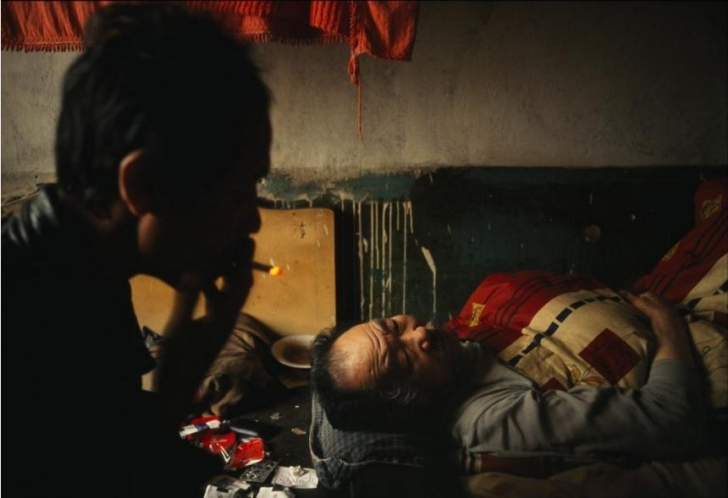 Çin'in Tiexi Sanayi Bölgesi'nde bir adam yatalak babası yanında uyurken bir sigara içiyor.