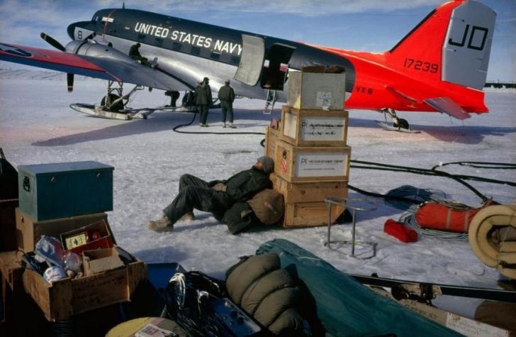 Antarktika'da geri kalan ekip uçuşa hazırlanırken bir adam kasalara yaslanarak dinleniyor.